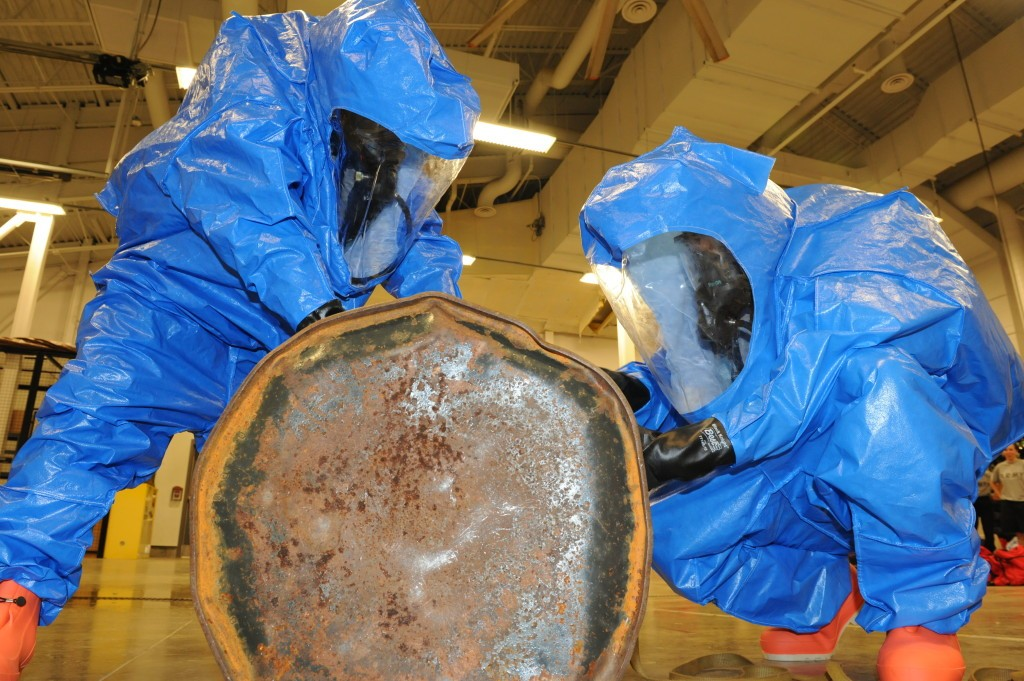 Soldiers work together to patch and plug a 55-gallon drum to stop a hazardous material leak during Advanced Leader Course incident. (Melissa Buckley, FLW Public Affairs)